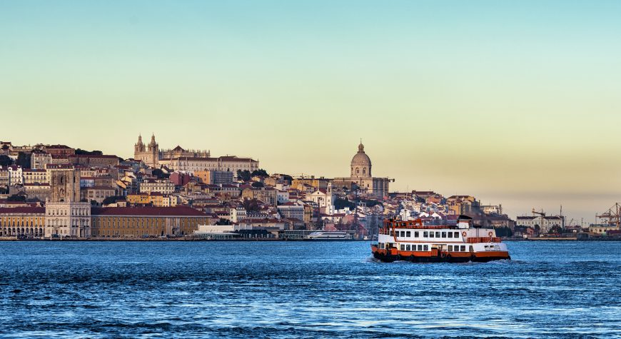 Passenger boat (Cacilheiro) in the Tagus River with the Lisbon skyline in the back